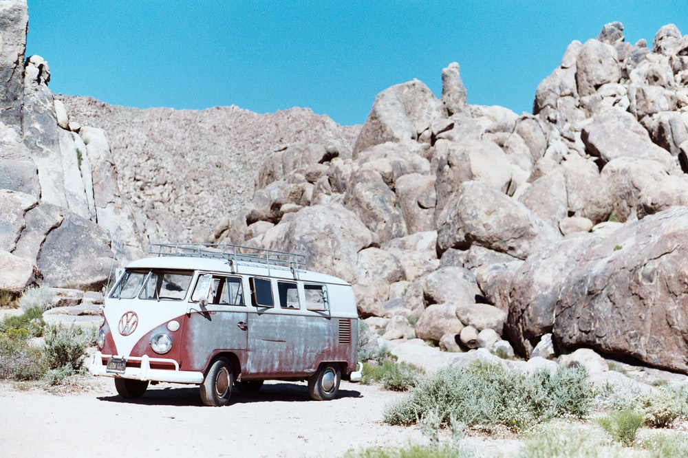 red and white Volkswagen T1 bus parked near rocks during daytime