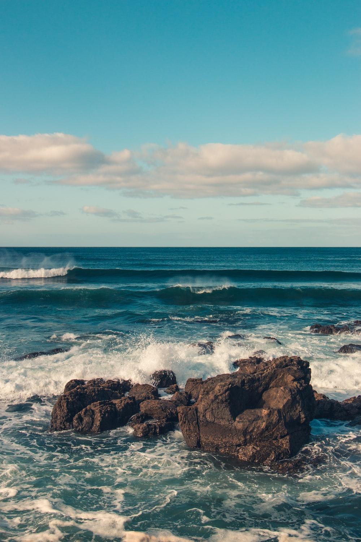 ocean wave splashing on rocks during daytime