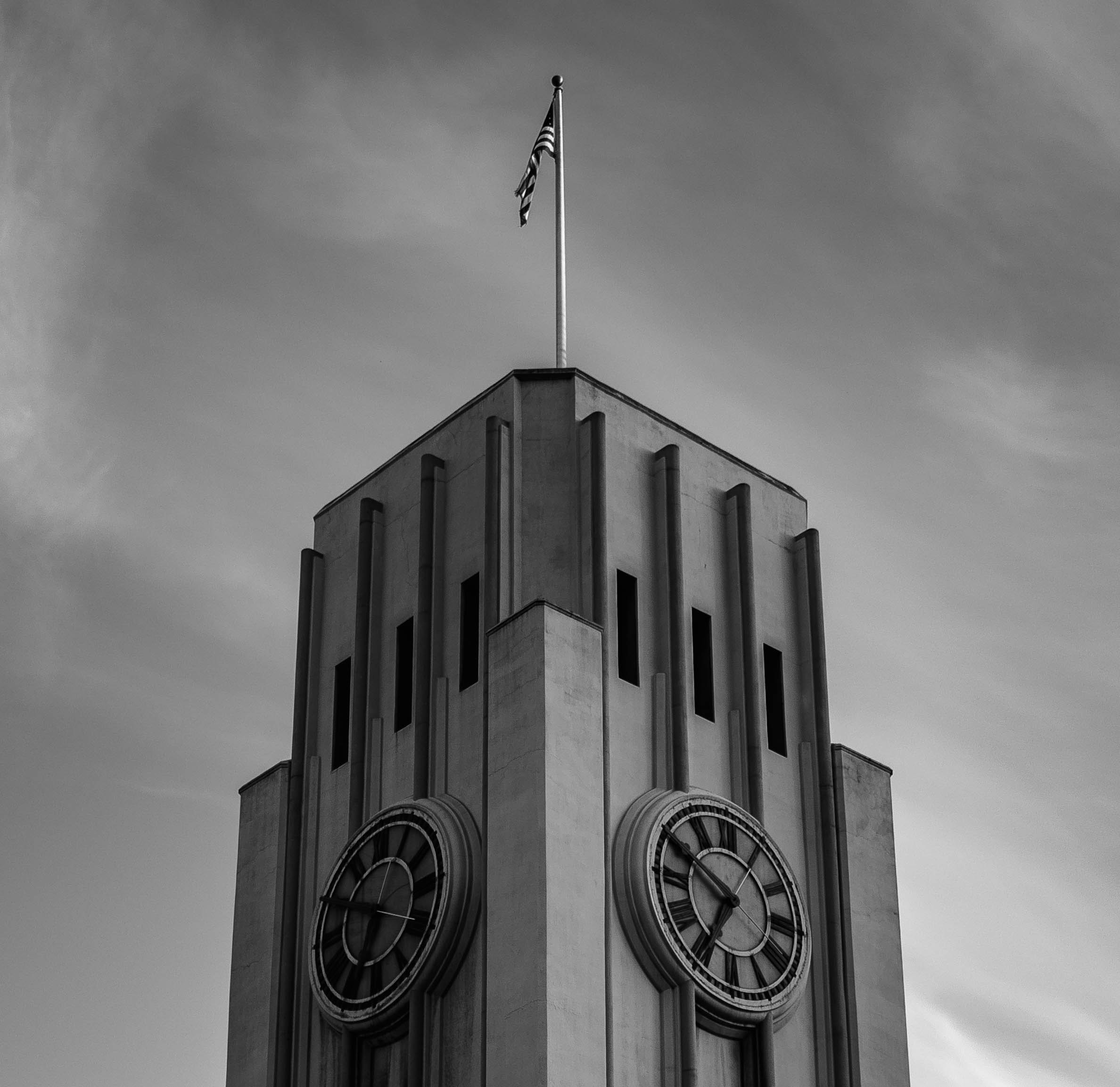 low-angle and grayscale photography of tower clock with raised flag