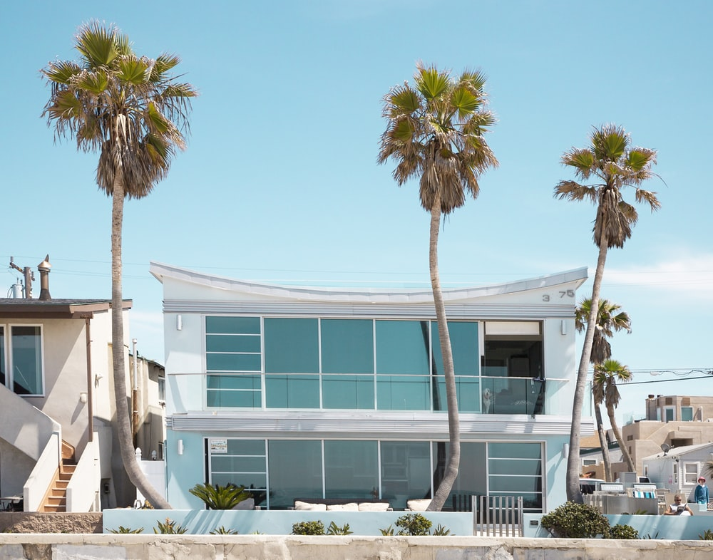 three palm trees in front of 2-story house