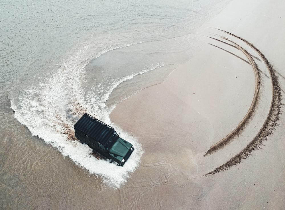 black off-road vehicle riding on seashore