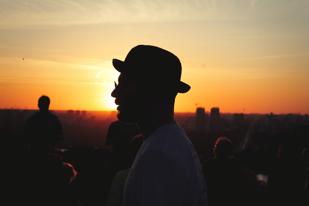 man wearing white shirt and black hat during golden hour