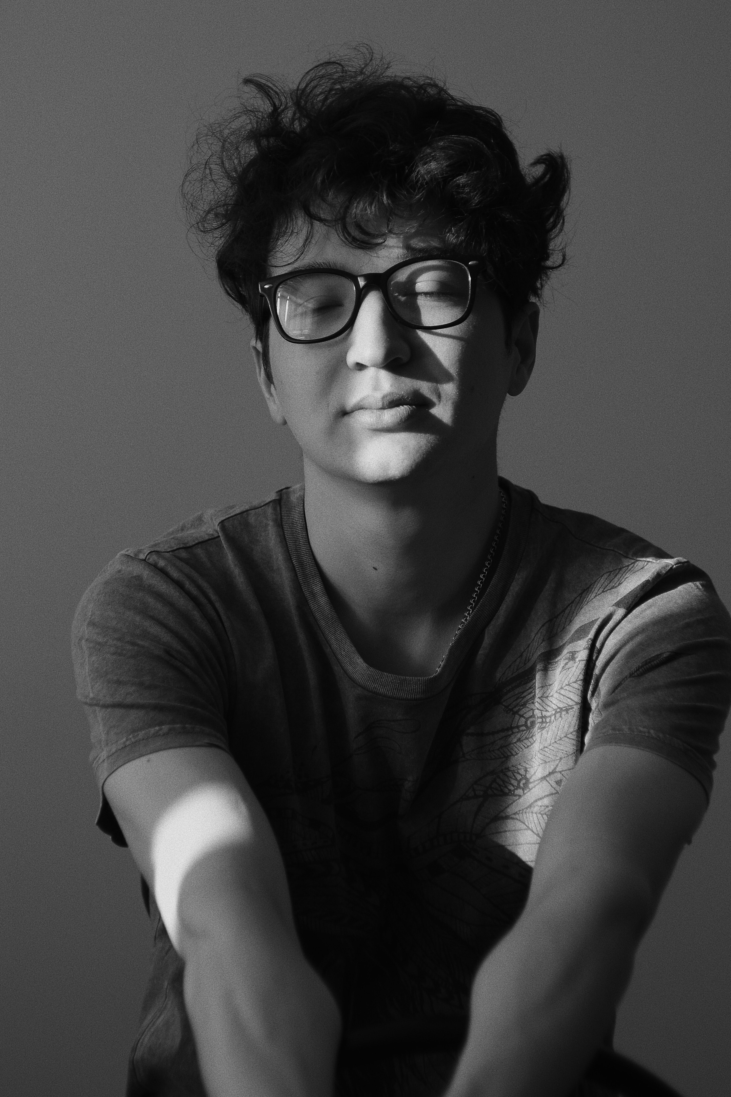 grayscale photography of man wearing crew-neck t-shirt and eyeglasses