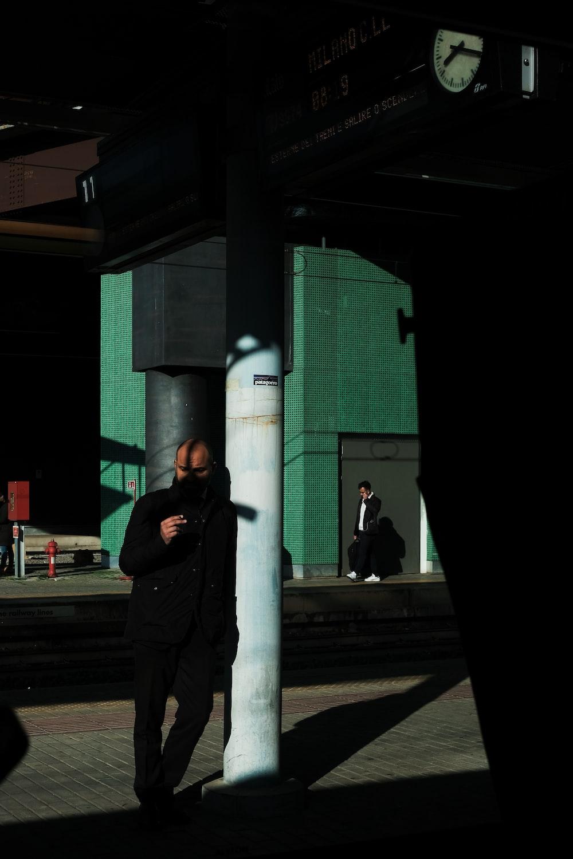 man wearing black jacket lying on teal concerete pillar