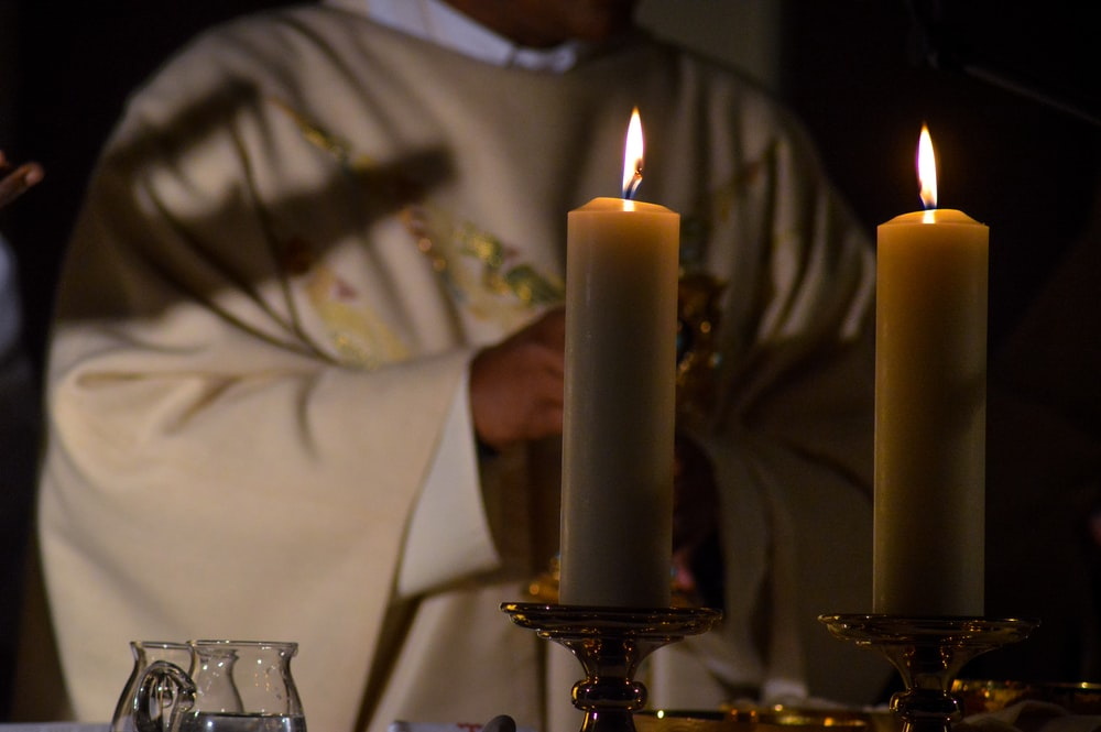 priest standing in front of lighted candles