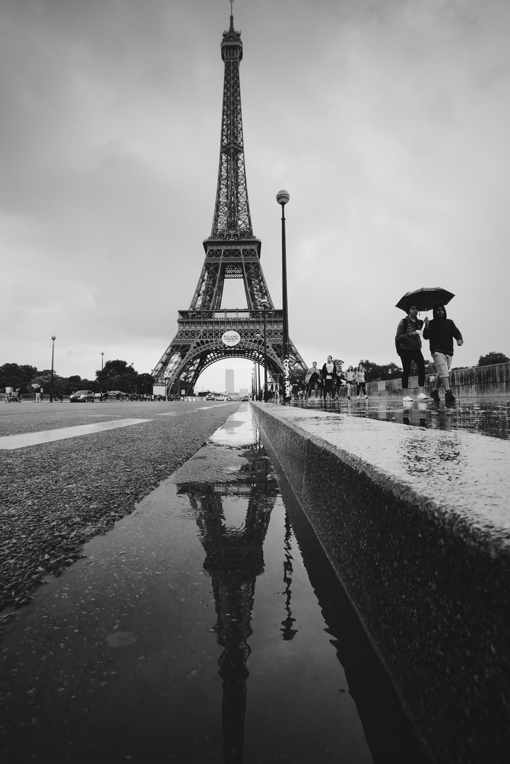 two women walking with umbrella from the Eiffel Tower