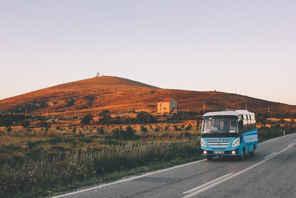 昼間の道路上の青いバス