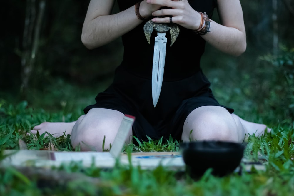 woman kneeling on grass holding knife