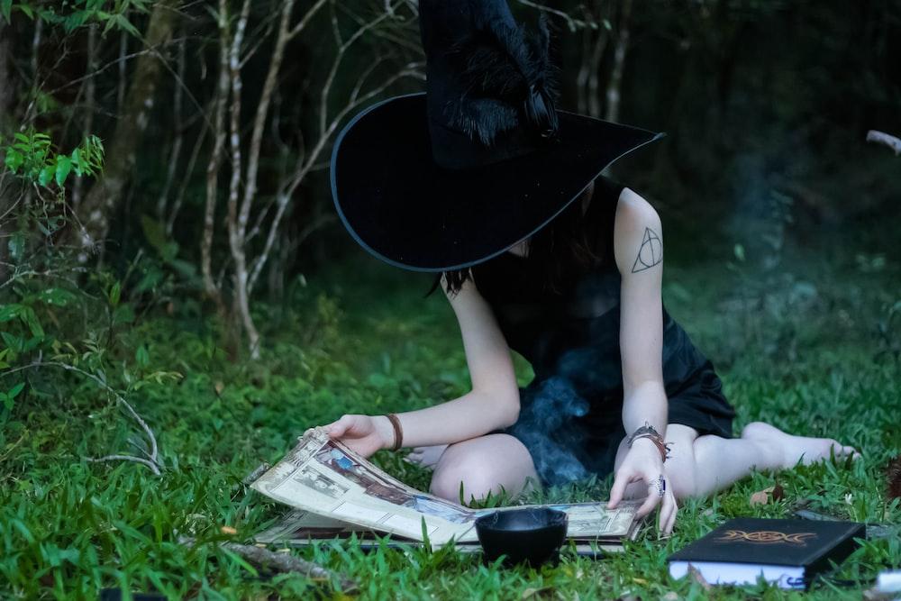 緑の芝生の芝生に座って本を読む女