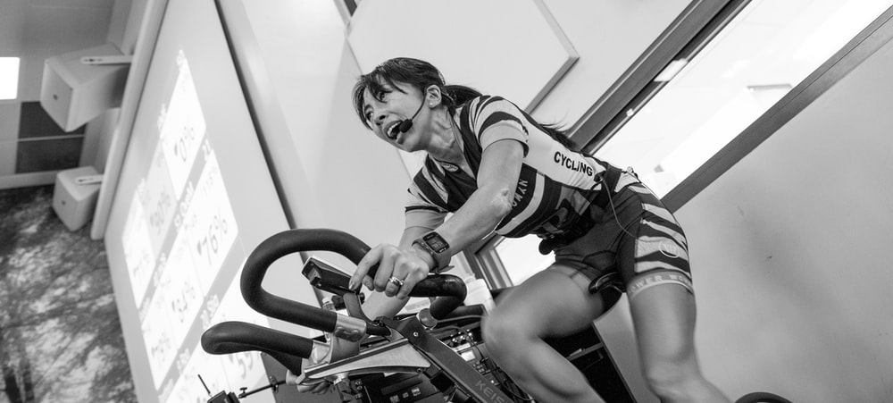 grayscale photography of woman on elliptical trainer