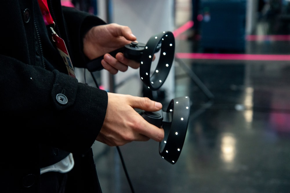 person holding black controllers