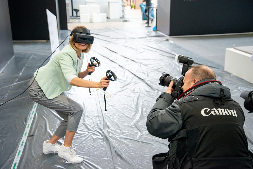 woman wearing virtual reality headset beside man holding camera