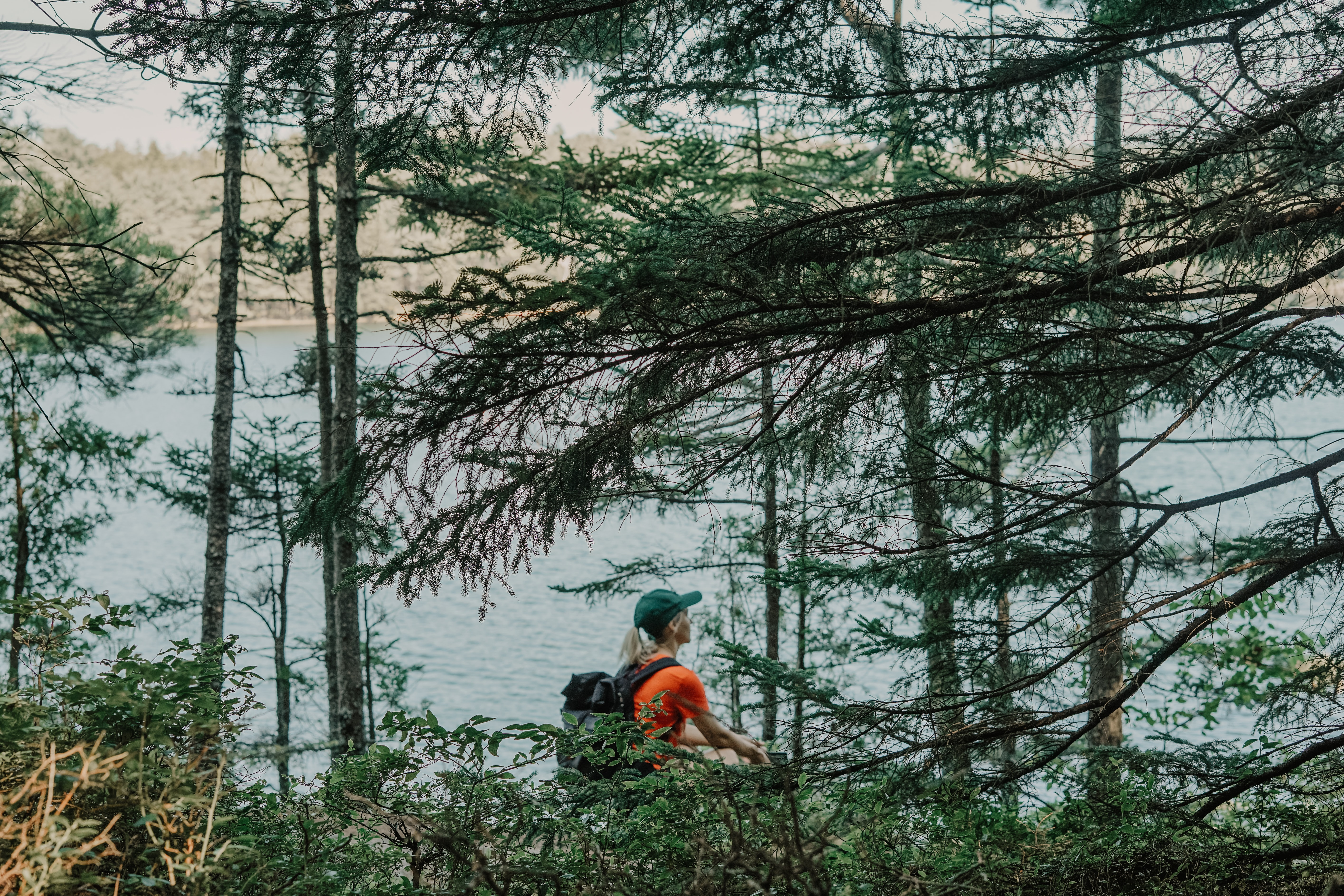 girl with backpack near the body of water during daytime