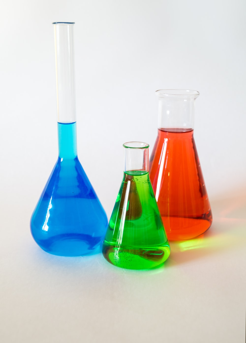 three assorted-color liquid-filled laboratory apparatuses