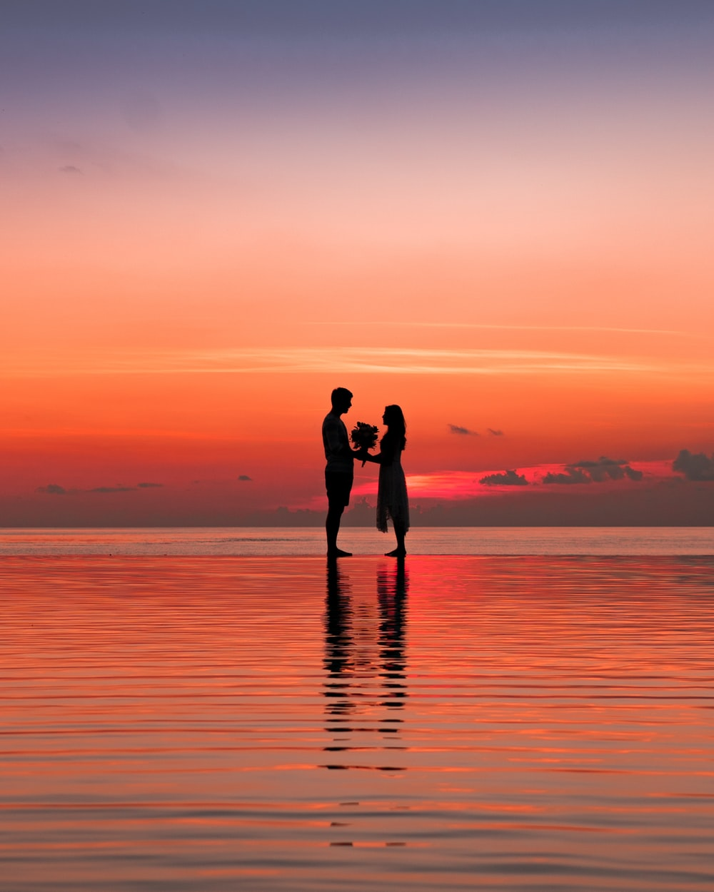 man and woman silhouette against golden hour