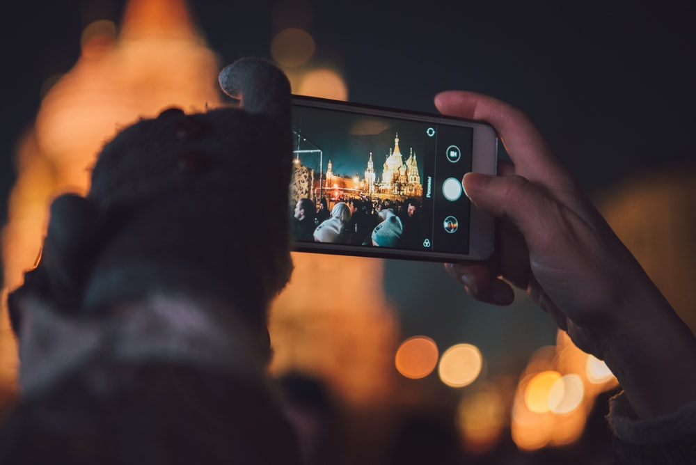 person taking picture of a building on it smartphone