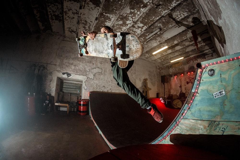 person holding skateboard jumping from skateboard ramp
