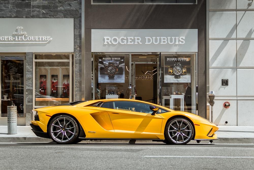 yellow Lamborghini coupe parked outside storefront