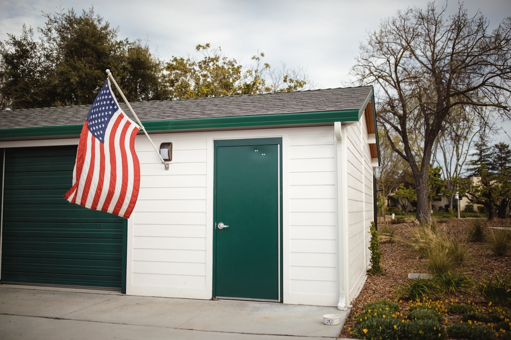 American flag outside white and green wooden house with closed door