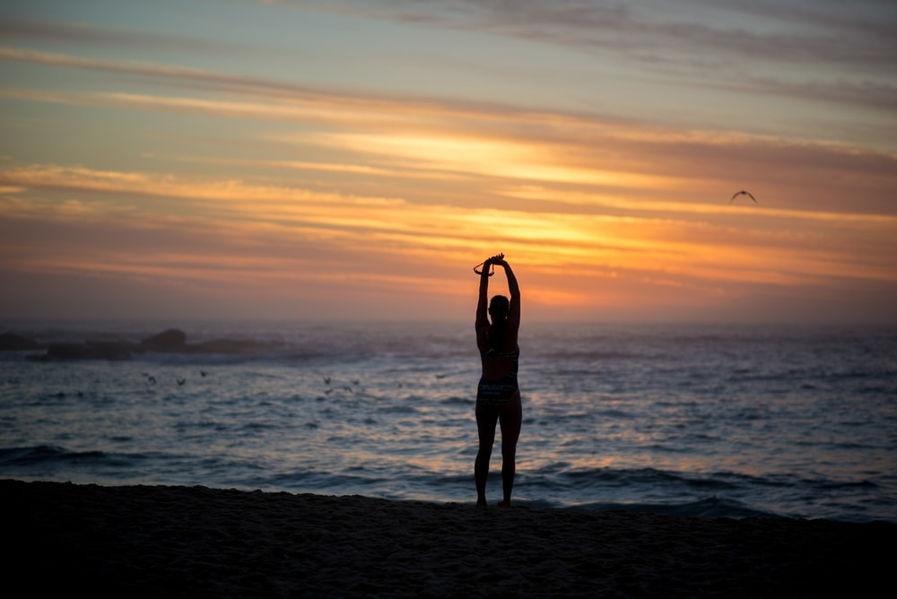 silhouette of woman standing beside seashore during sunset