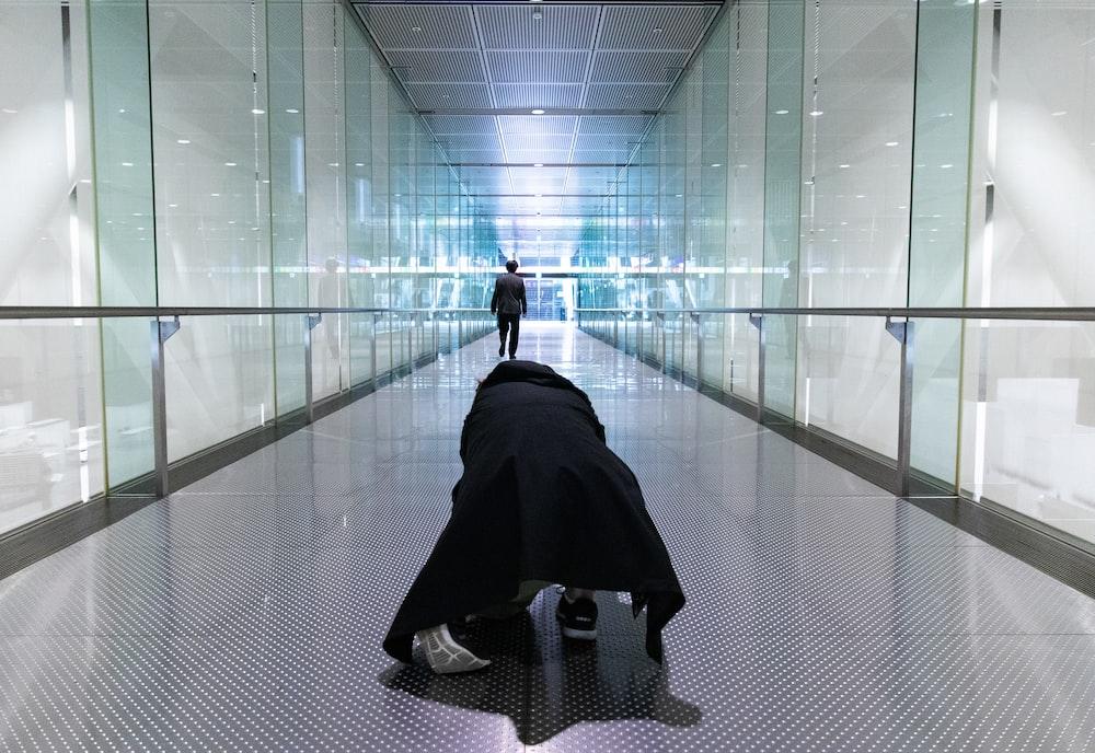 person kneeling on hallway