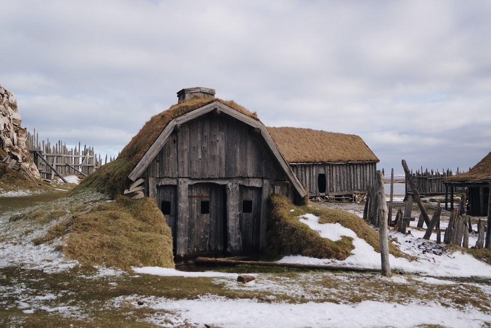 gray wooden house near sea under white skies
