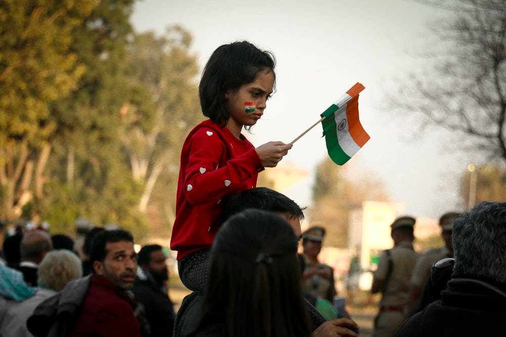 girl sitting on neck of man while holding mini India flag surrounded with people