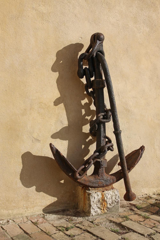 brass anchor near beige wall