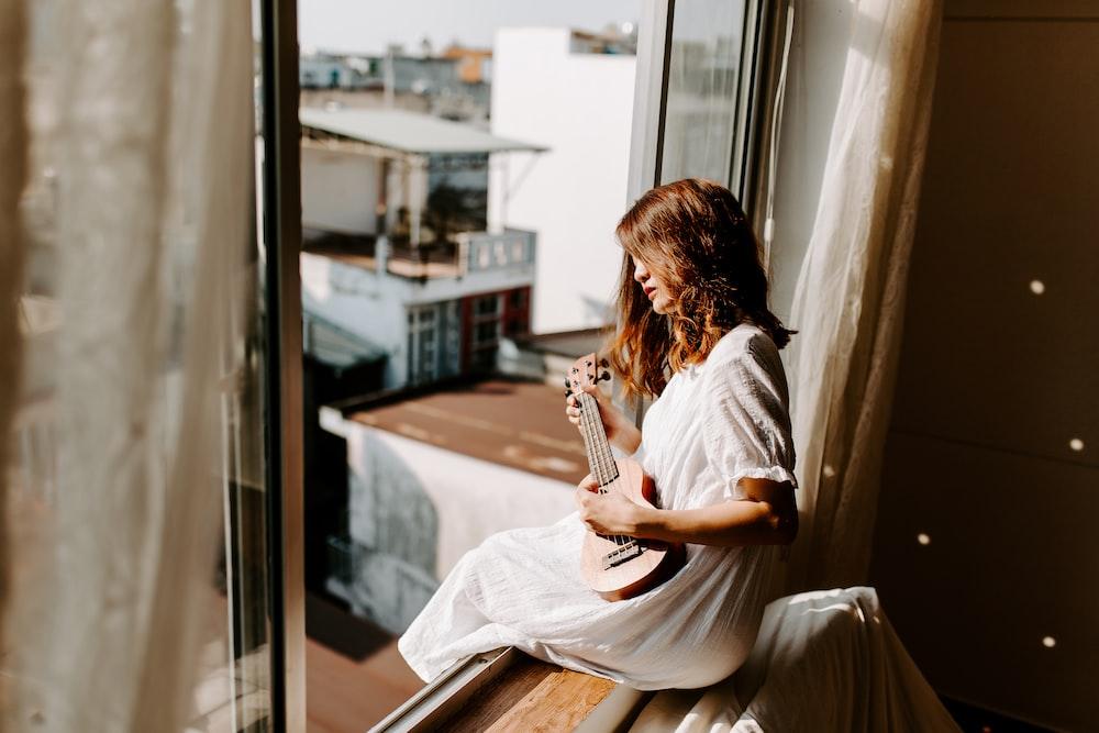 woman sitting on window inside room,