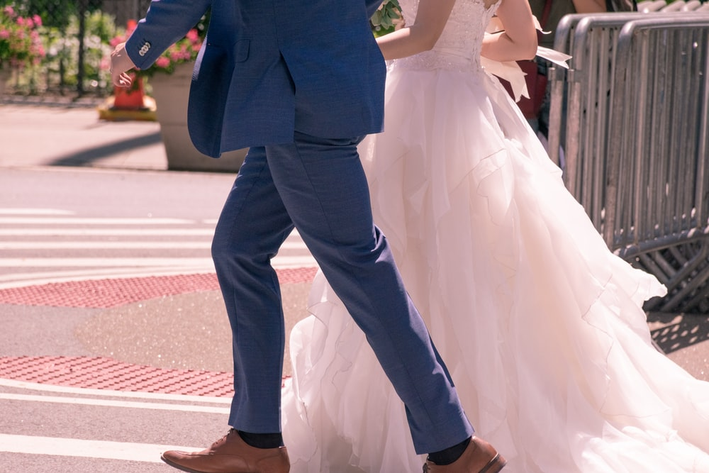 two people wearing wedding dresses walking near metal frames