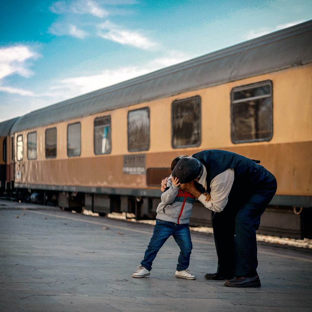 man and boy playing beside train