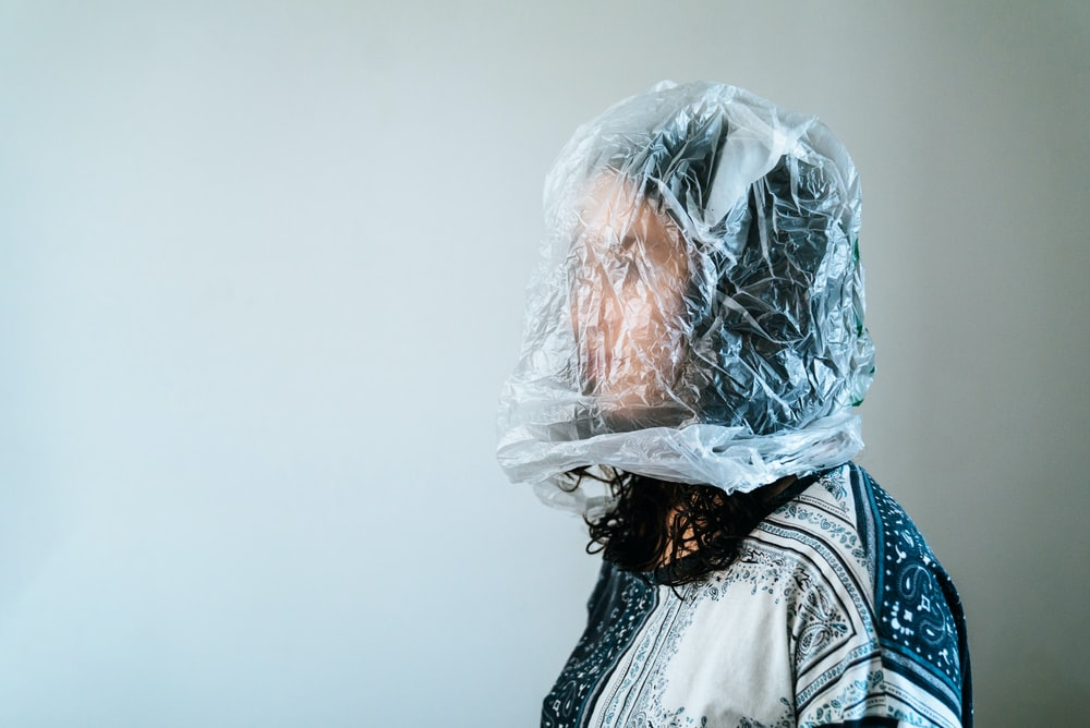 woman in white and blue floral shirt with clear plastic bag on face