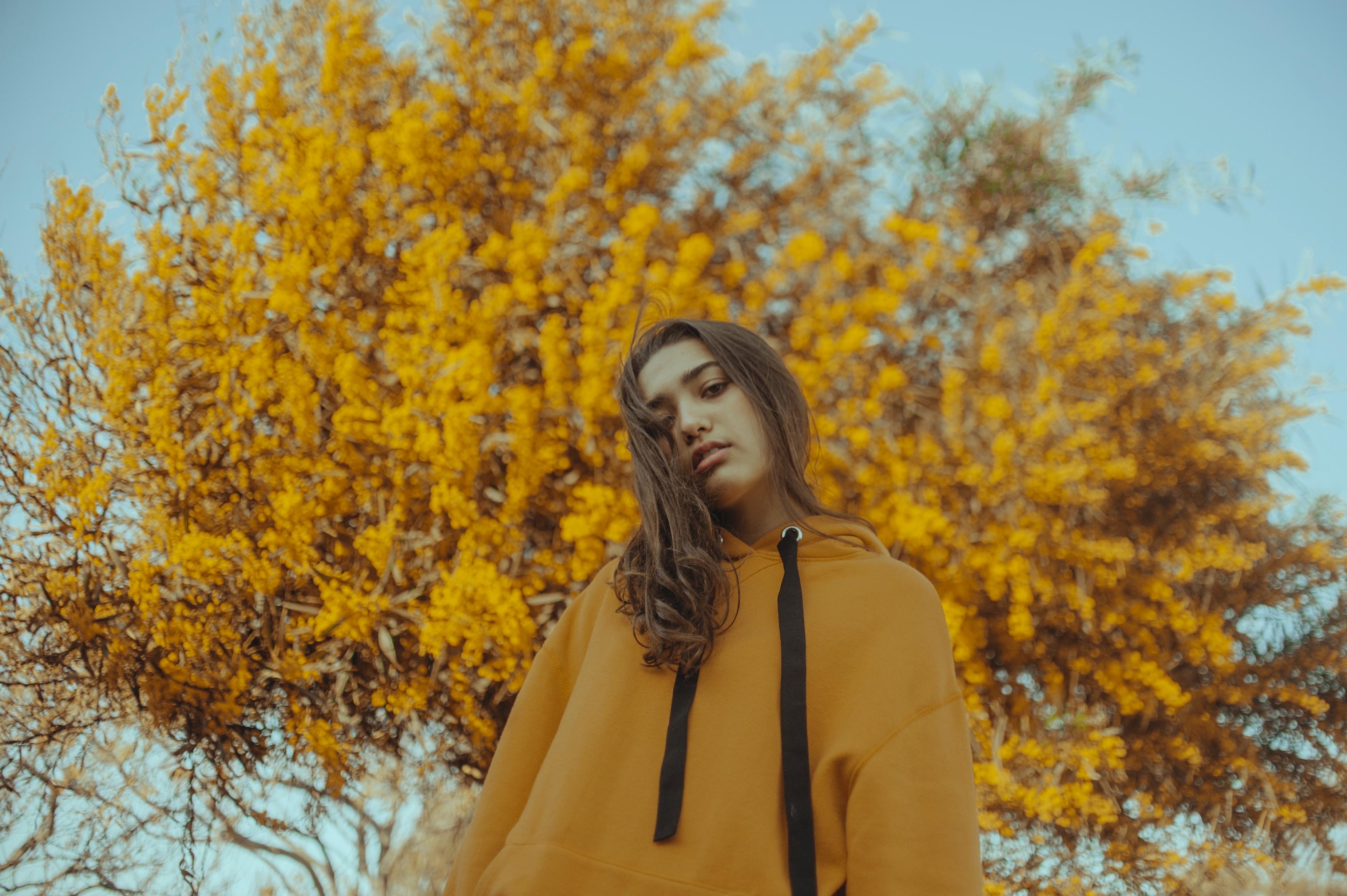 woman standing near yellow tree
