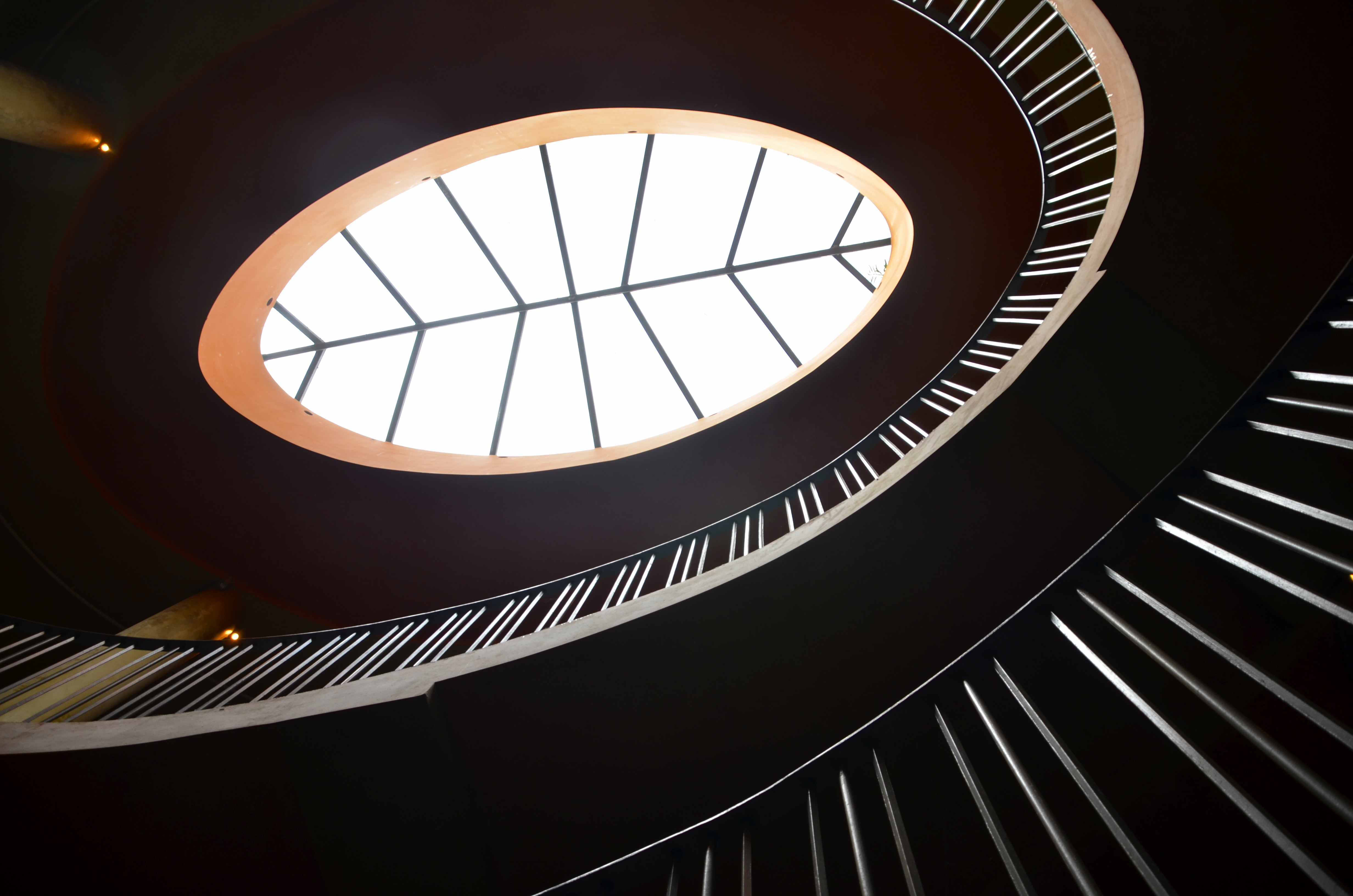 grey spiraling staircase in clear glass center ceiling building