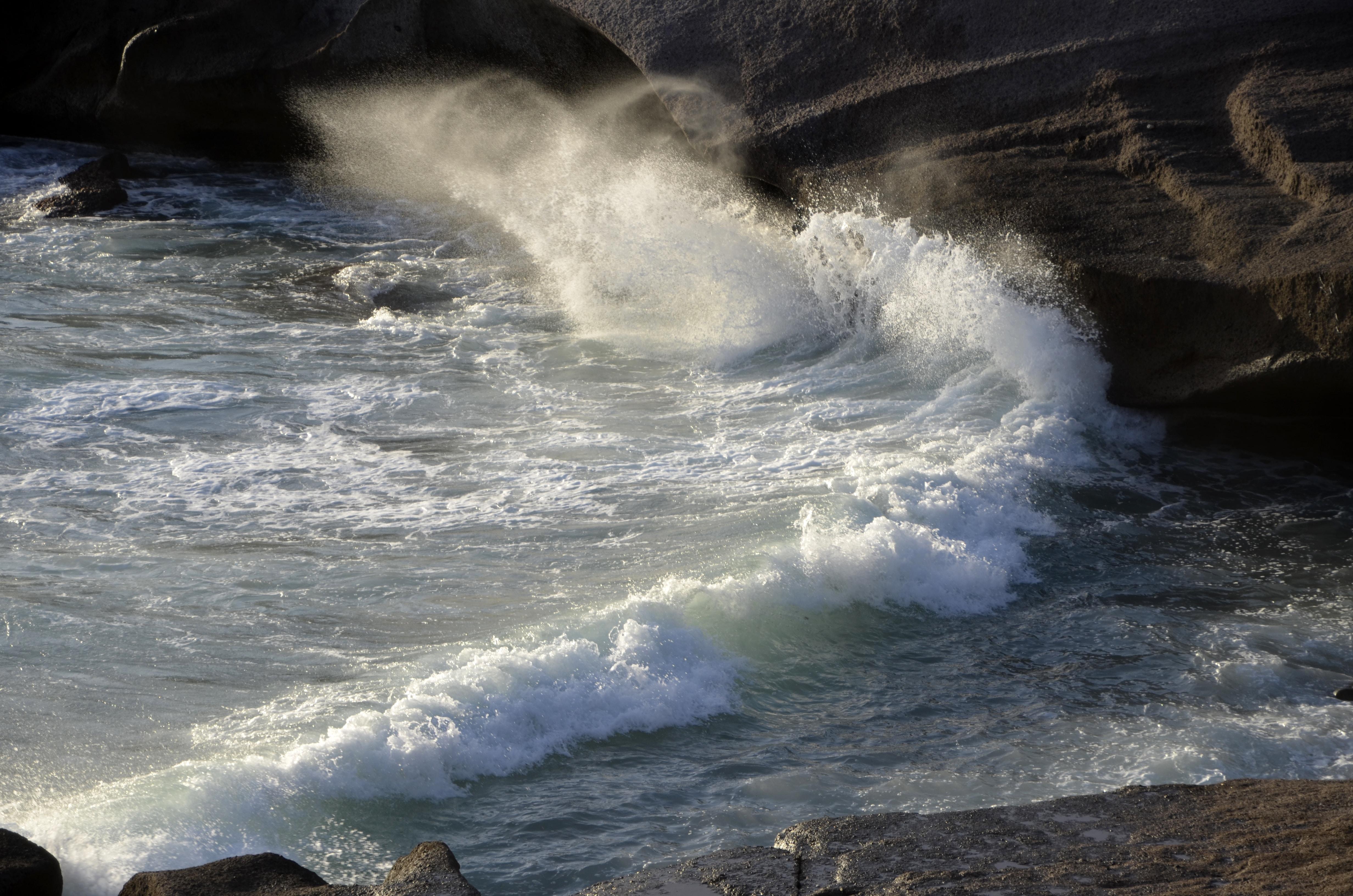 sea wave splashing on rocks during daytime