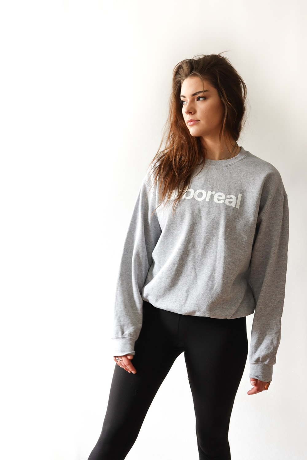 standing woman in gray sweater and black pants