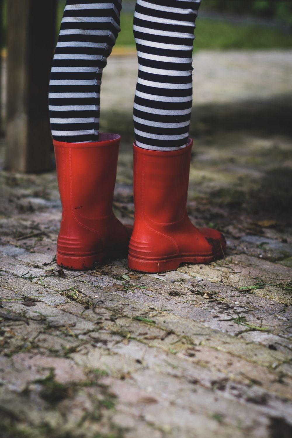 person wearing black and white striped socks and red rain boots standing on concrete pavement