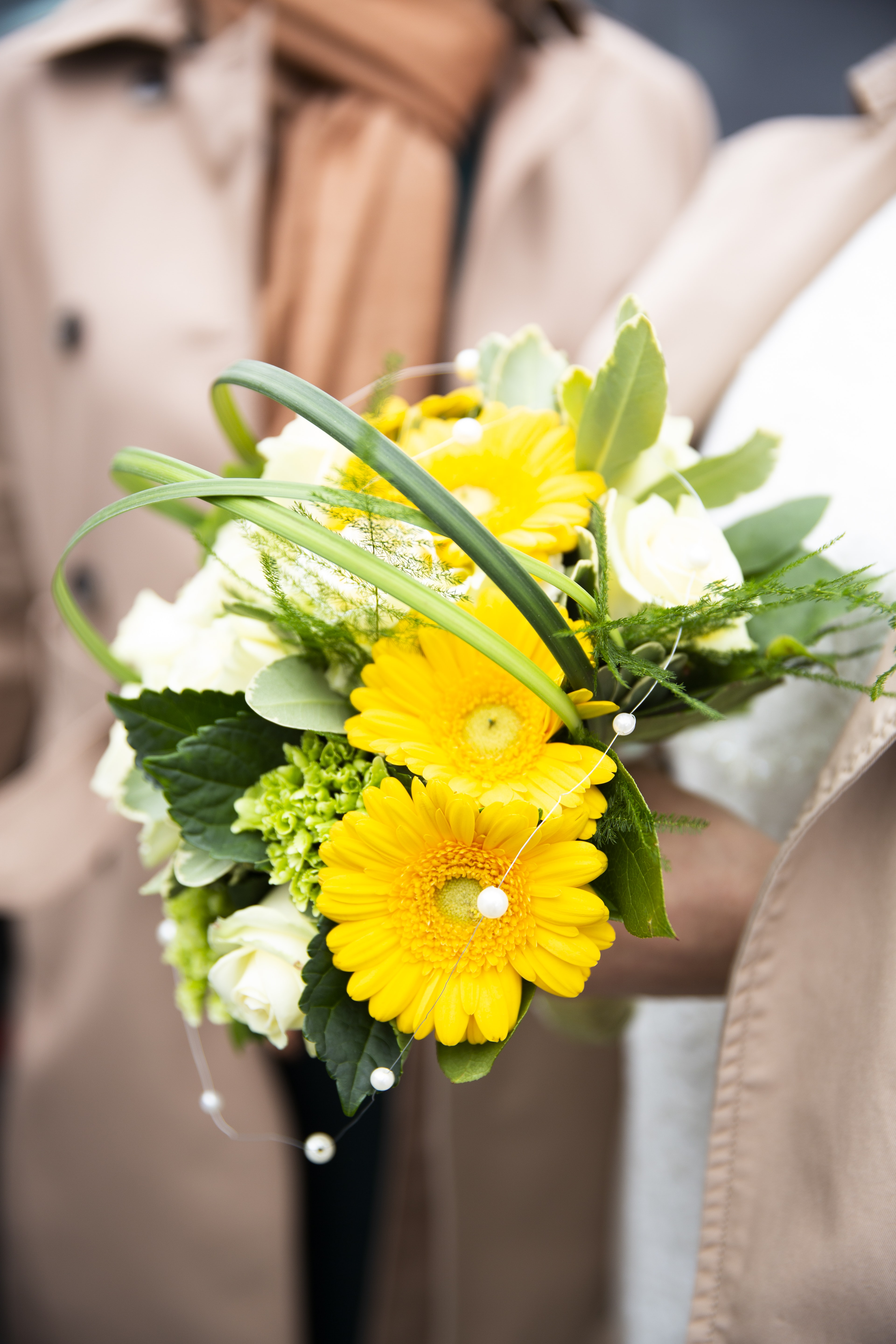 person holding yellow petaled flowers