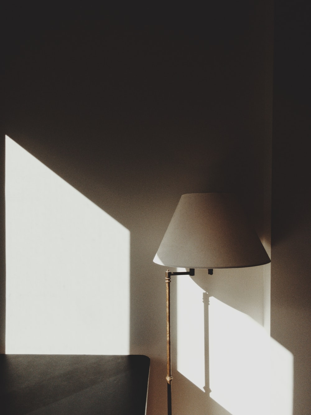 white and gray floor lamp beside wall