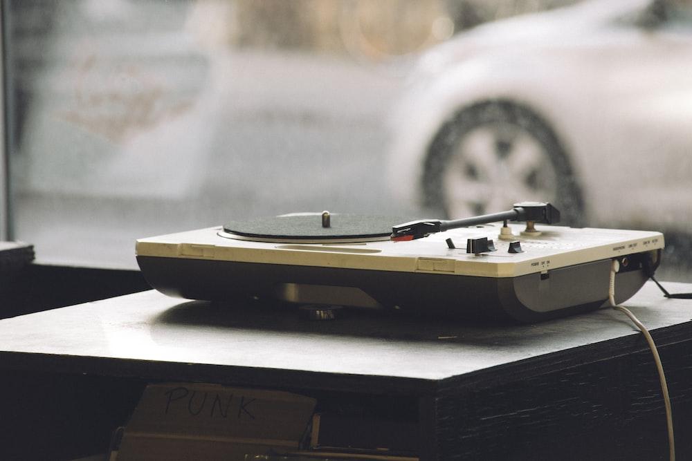 beige and black DJ turntable on black surface
