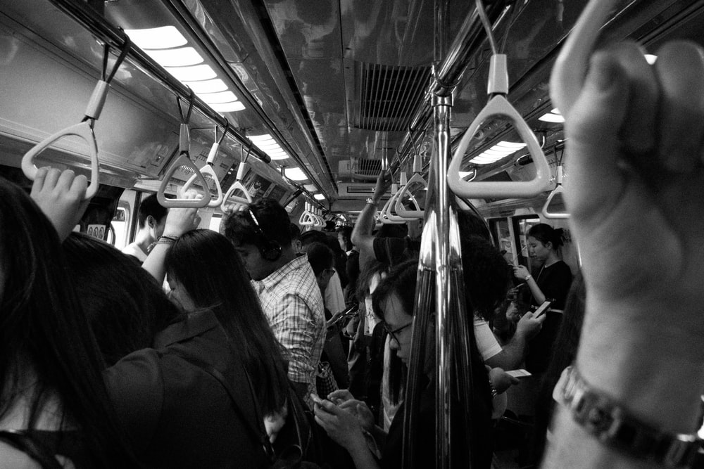 grayscale photo of people inside train