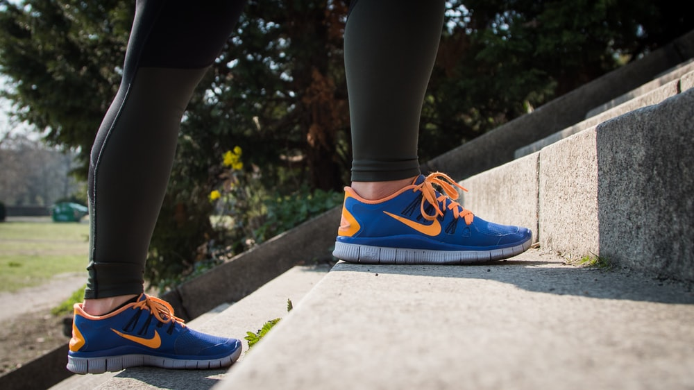 person wearing blue Nike sneakers
