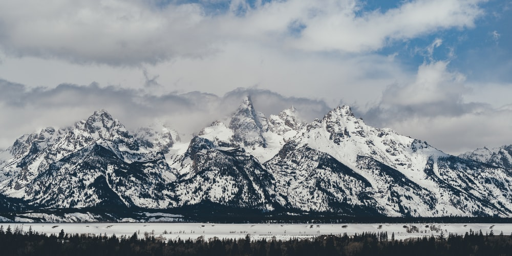 snow covered mountain and valley under white cloudy sky