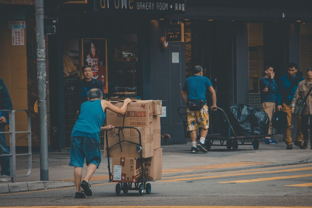 man wearing blue tank top pushing the hand truck with cardboard box