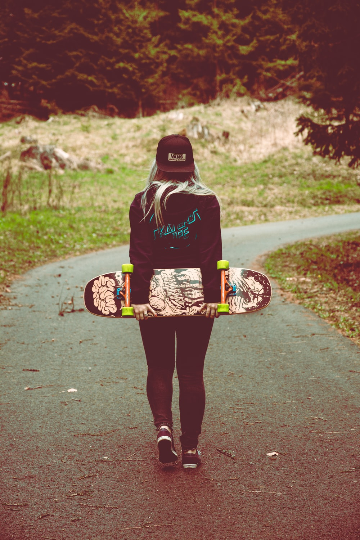 woman carrying skateboard walking on pathway