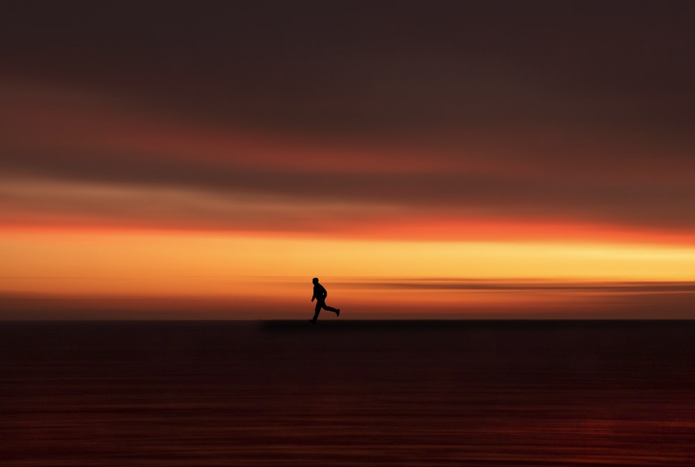 silhouette of person walking on the field during sunset