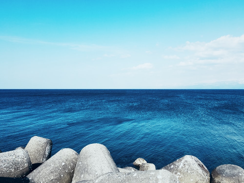 rock formation beside blue body of water