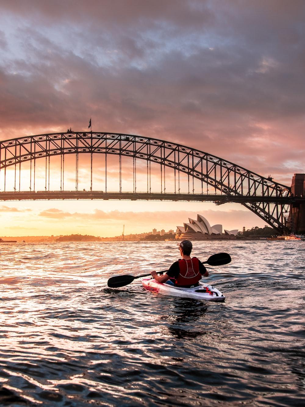 person riding kayak towards metal bridge