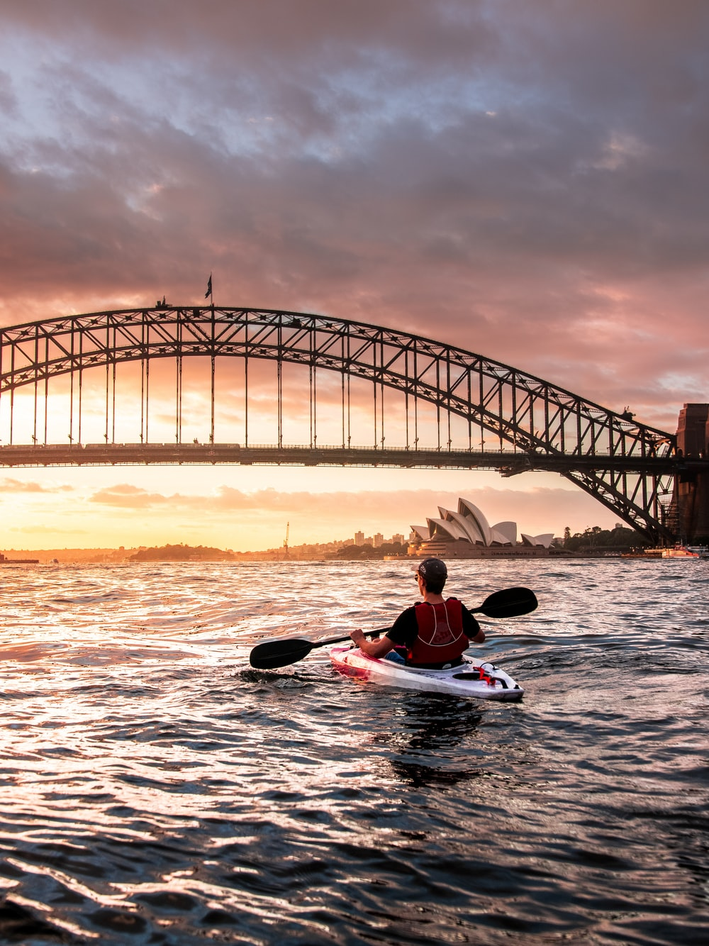 person riding kayak towards metal bridge