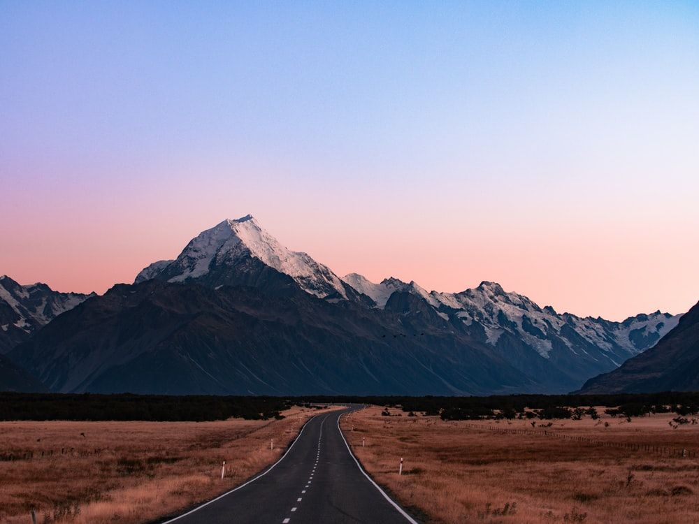 snow-capped mountains near concrete road